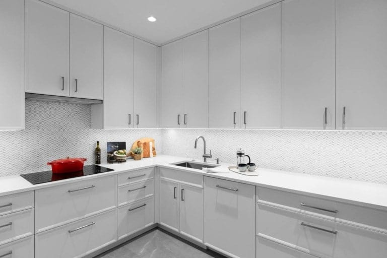 The rest of the kitchen is bright and white with a lighting underneath the floating cabinets.