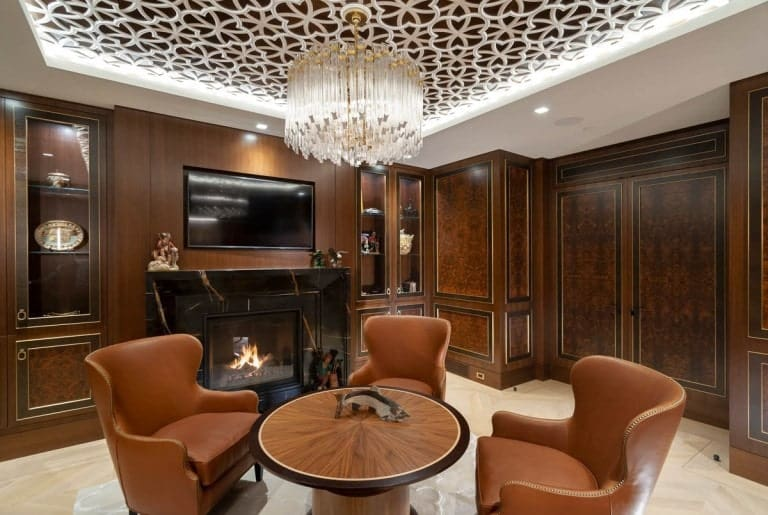 On the side of the chairs and table is a large fireplace topped with a wall-mounted TV.
