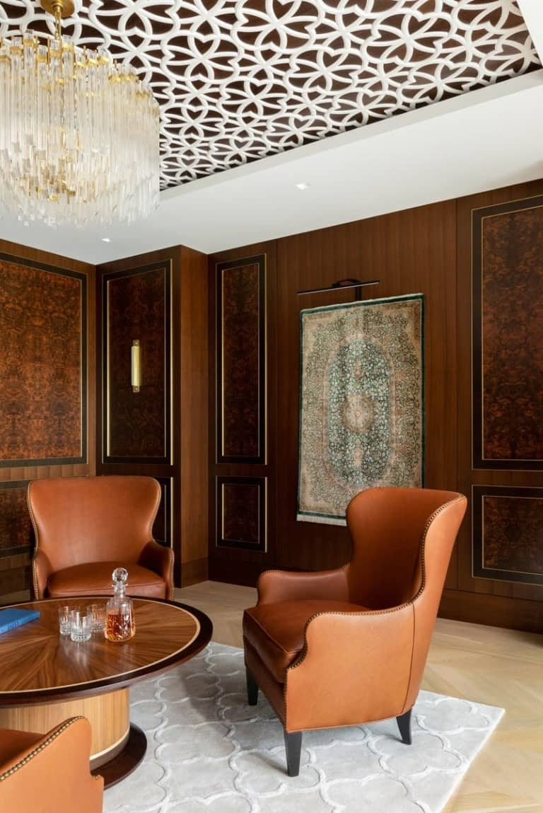 This is a large wood-paneled den with brown leather chairs and a round wooden table.