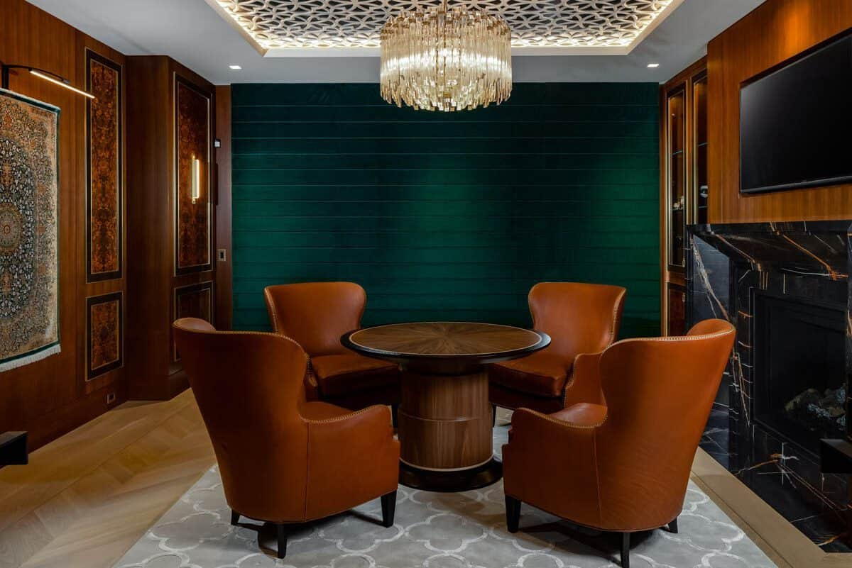 The four leather armchairs and round wooden table is topped with a detailed tray ceiling that has a crystal lighting in the middle.
