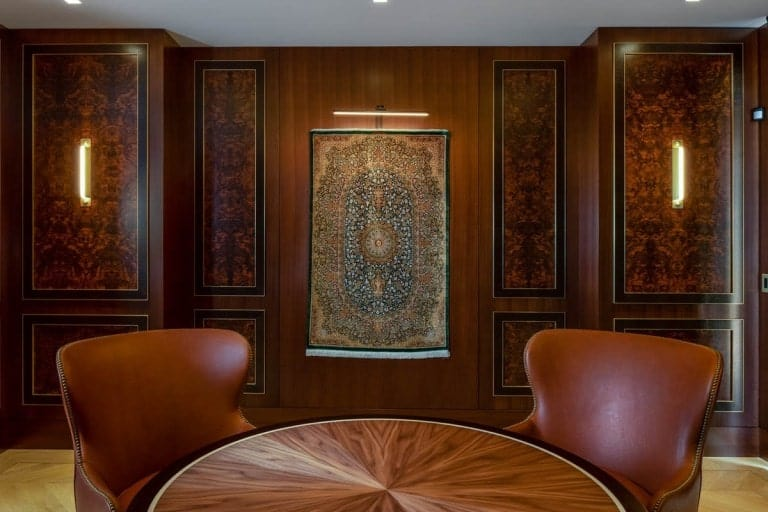 This is a close look at the wood-paneled wall of the den adorned with a tapestry and lit by wall-mounted lighting.