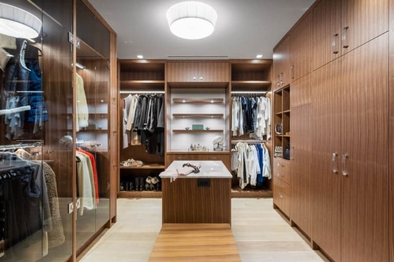 This is the large walk-in closet with wooden structures on its walls with shelves, cabinets and drawers and a light hardwood flooring.