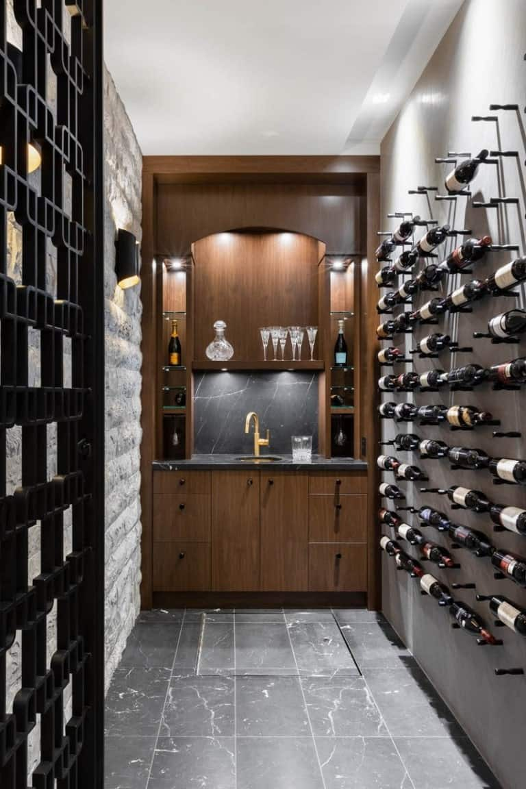 This is the long and narrow wine cellar with small black wall-mounted structures for wine storage and a wooden built-in structure at the far end with cabinets and shelves.