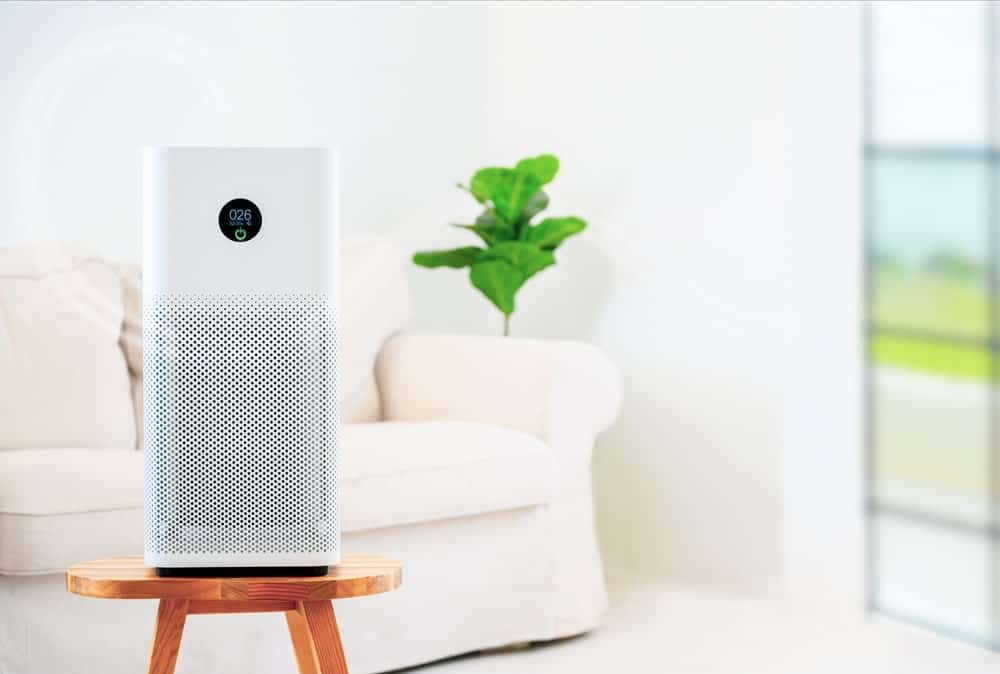 A white air purifier placed in the middle of the living room.