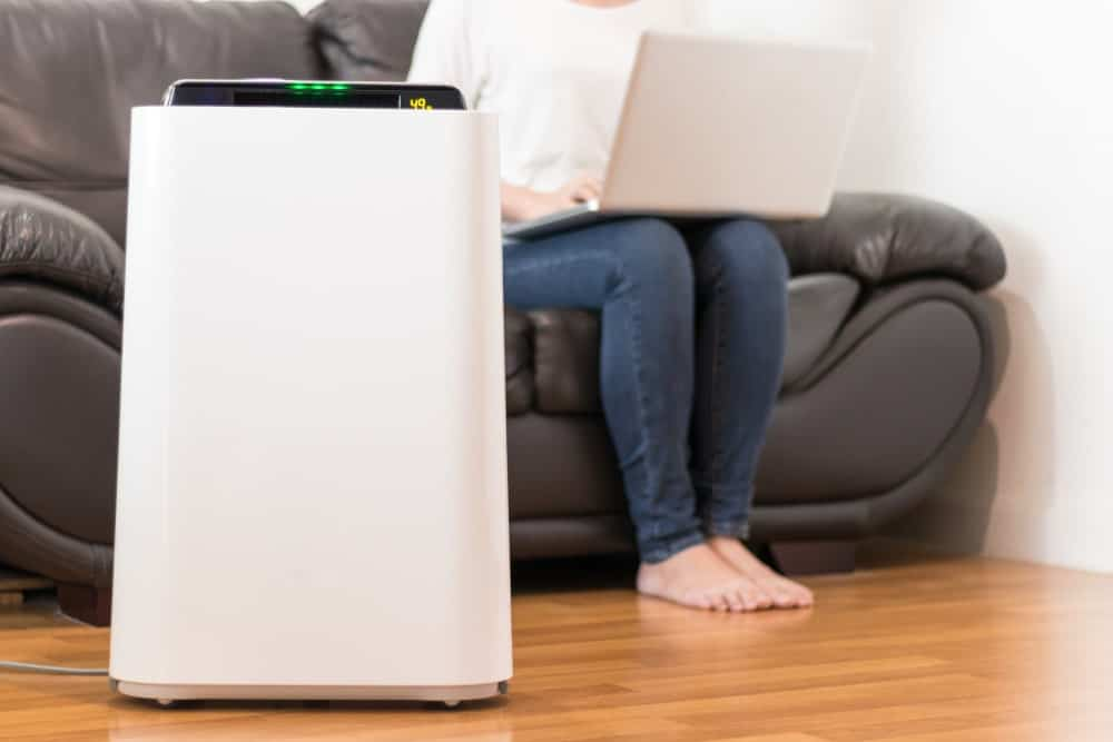 A close look at a white air purifier on the floor in the living room.