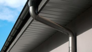 A close look at a house's rain gutter and drain pipe.