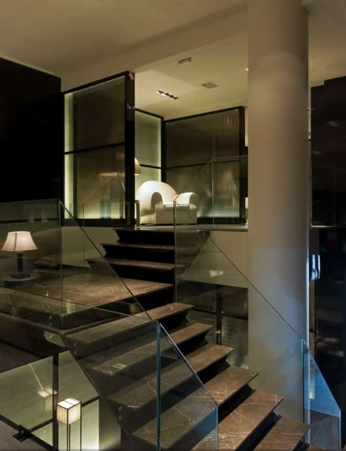The set of steps that has glass railings lead to the small area at the top with a beige armchair lit by its side lamp.