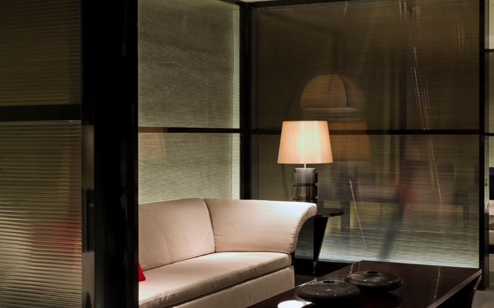 This is a close look at a beige sofa display adorned by the warm lighting from the table lamp on the side table.