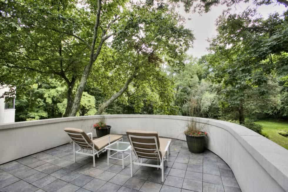 This is the concrete balcony with a couple of lounge chairs facing the lush landscape filled with tall trees and shrubs. Image courtesy of Toptenrealestatedeals.com.