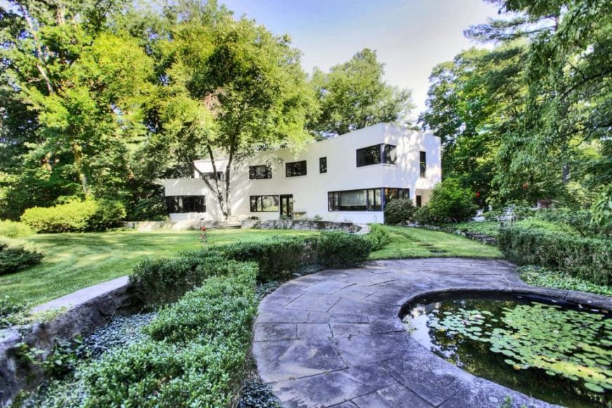This is an exterior look at the house with a modern design complemented by its bright white exterior walls and glass windows that make it stand out against the surrounding green landscaping with tall trees, grass lawns and shrubs. Image courtesy of Toptenrealestatedeals.com.