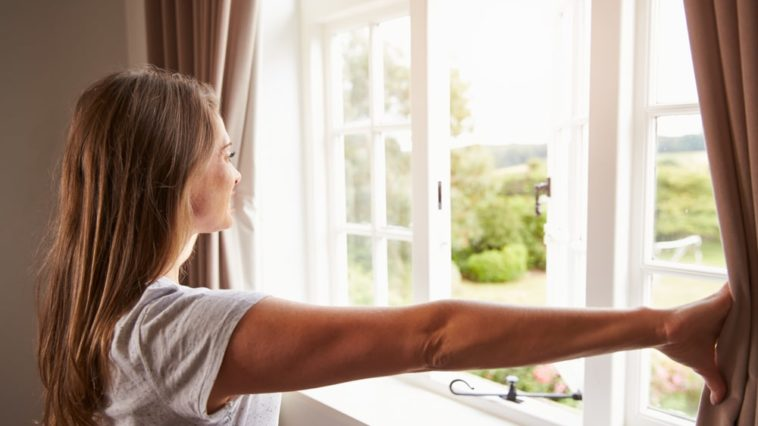 A woman pushing aside the curtains to let in natural lighting.