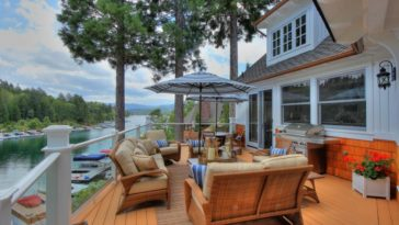 This is the wooden deck terrace of the house overlooking the lake. You can see here that the large area is fitted with an outdoor sitting area and dining area along with a grilling station. This also shows the exteriors of the house that has bright walls and glass windows. Image courtesy of Toptenrealestatedeals.com
