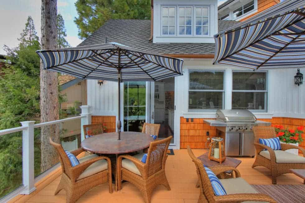 This is the wooden deck terrace of the house overlooking the lake. It has an outdoor dining area and a grilling station surrounded by glass railings. Image courtesy of Toptenrealestatedeals.com