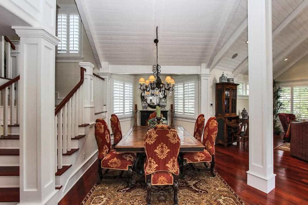The dining area is just on the side of the staircase. It has a long wooden dining table surrounded by red patterned chairs and topped with a small dark chandelier. Image courtesy of Toptenrealestatedeals.com