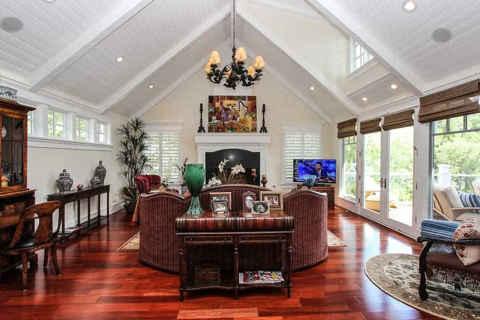 This is the living room with a tall cathedral ceiling and a dark chandelier over the sofa set that faces the large fireplace on the far wall topped with a painting. Image courtesy of Toptenrealestatedeals.com