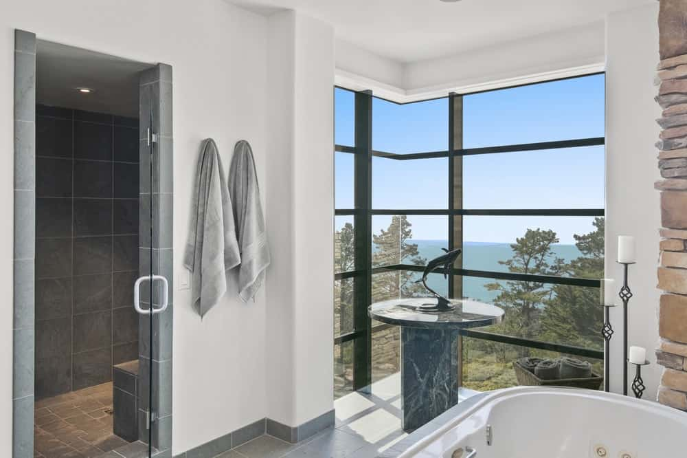 This view of the primary bathroom showcases the freestanding bathtub, glass windows and the walk-in shower area. Image courtesy of Toptenrealestatedeals.com.