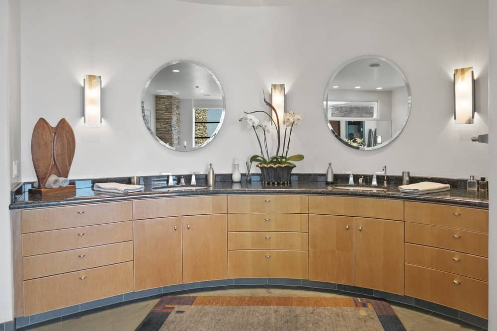 The large primary bathroom has a large curved wooden vanity topped with mirrors and sconces in between. Image courtesy of Toptenrealestatedeals.com.
