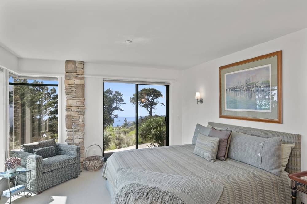 This other bedroom has a large gray bed topped with a painting mounted on the beige wall. Image courtesy of Toptenrealestatedeals.com.