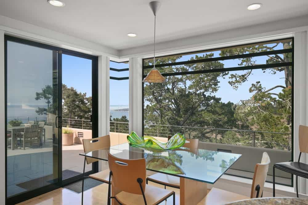 This is the breakfast nook just a few steps from the kitchen. It has a glass-top dining table to match the surrounding glass walls and doors. Image courtesy of Toptenrealestatedeals.com.