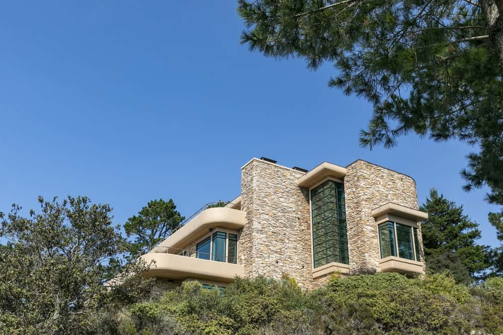 This is an exterior view of the back of the house showcasing the mosaic stone walls that are complemented by the massive glass walls. Image courtesy of Toptenrealestatedeals.com.