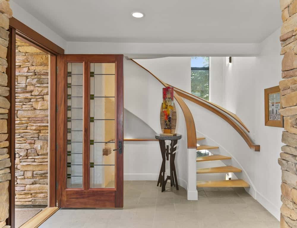 Upon entry of the house, you welcomed by this foyer with simple wooden and white tones. The side of the curved staircase is a decorative vase on a pedestal. Image courtesy of Toptenrealestatedeals.com.