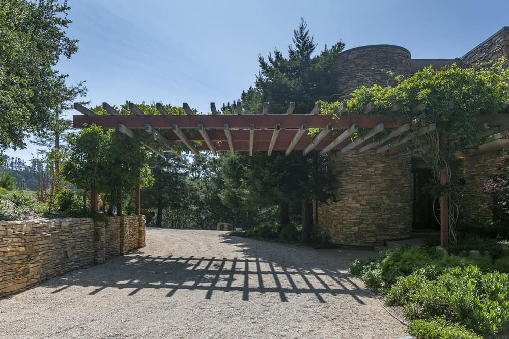 This is the front view of the house showcasing the driveway by the main entrance of the house that is adorned with trellises and shrubs. Image courtesy of Toptenrealestatedeals.com.