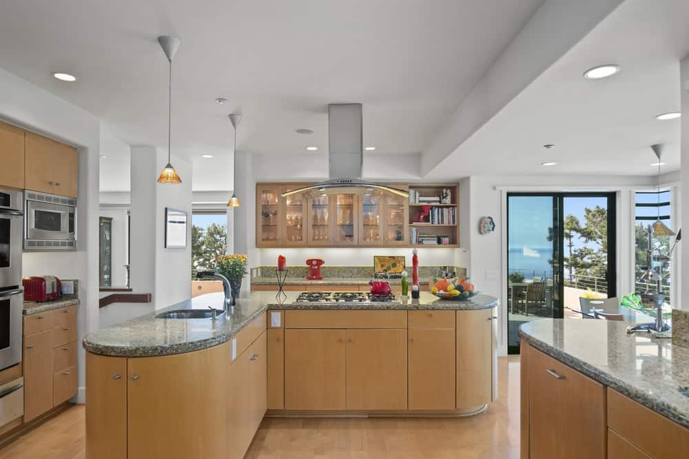The wooden tone of the kitchen's cabinetry matches perfectly with the light hardwood flooring. These are then complemented by the white ceiling. Image courtesy of Toptenrealestatedeals.com.