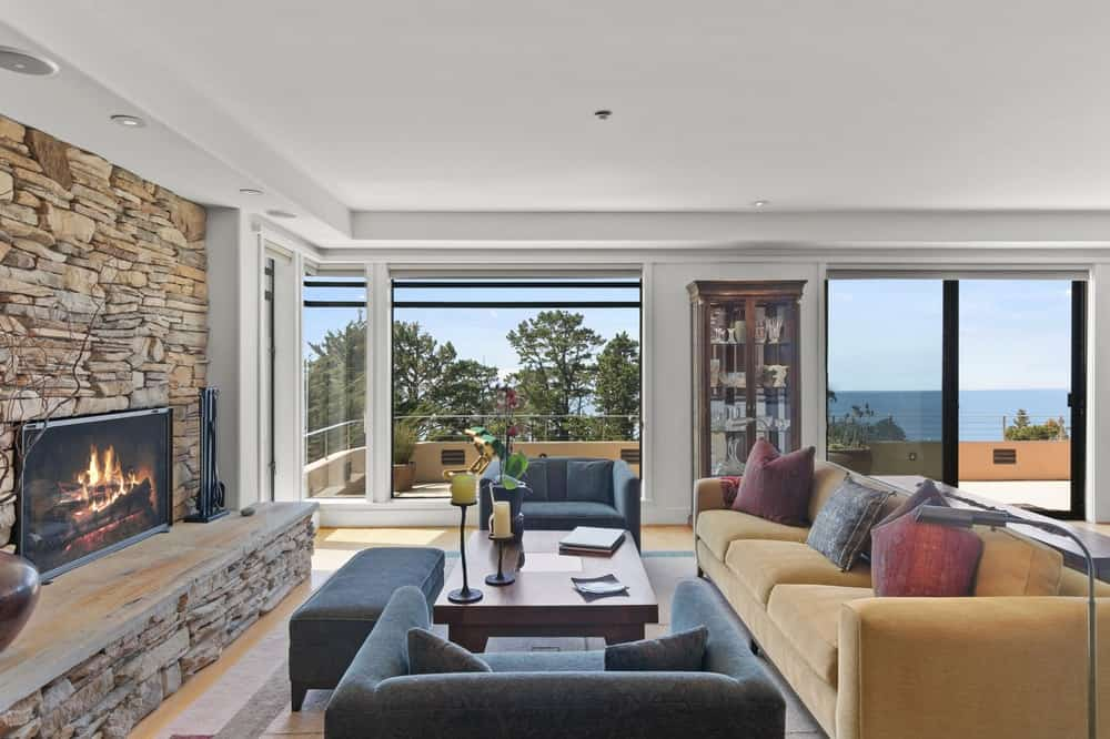 This closer view of the living room allows for a look at the stone fireplace across from the sofa and coffee table. Image courtesy of Toptenrealestatedeals.com.