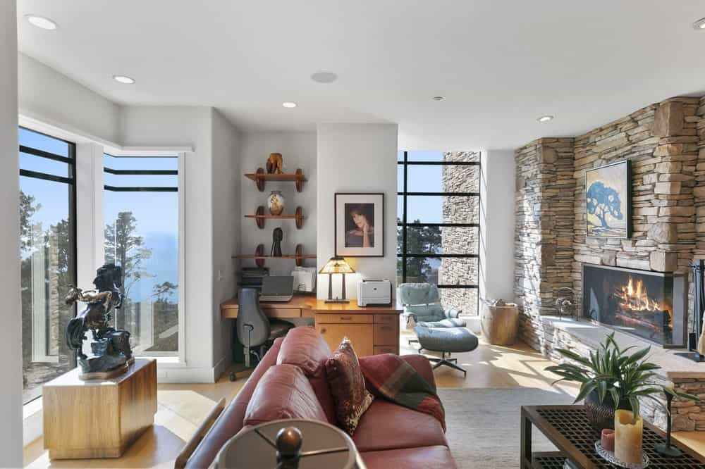 This is the spacious home office with glass walls that brighten the wooden desk and sofa of the sitting area across from the fireplace. Image courtesy of Toptenrealestatedeals.com.