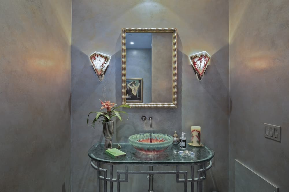 This is the small powder room of the house with a glass-top vanity topped with a mirror that is flanked by sconces. Image courtesy of Toptenrealestatedeals.com.