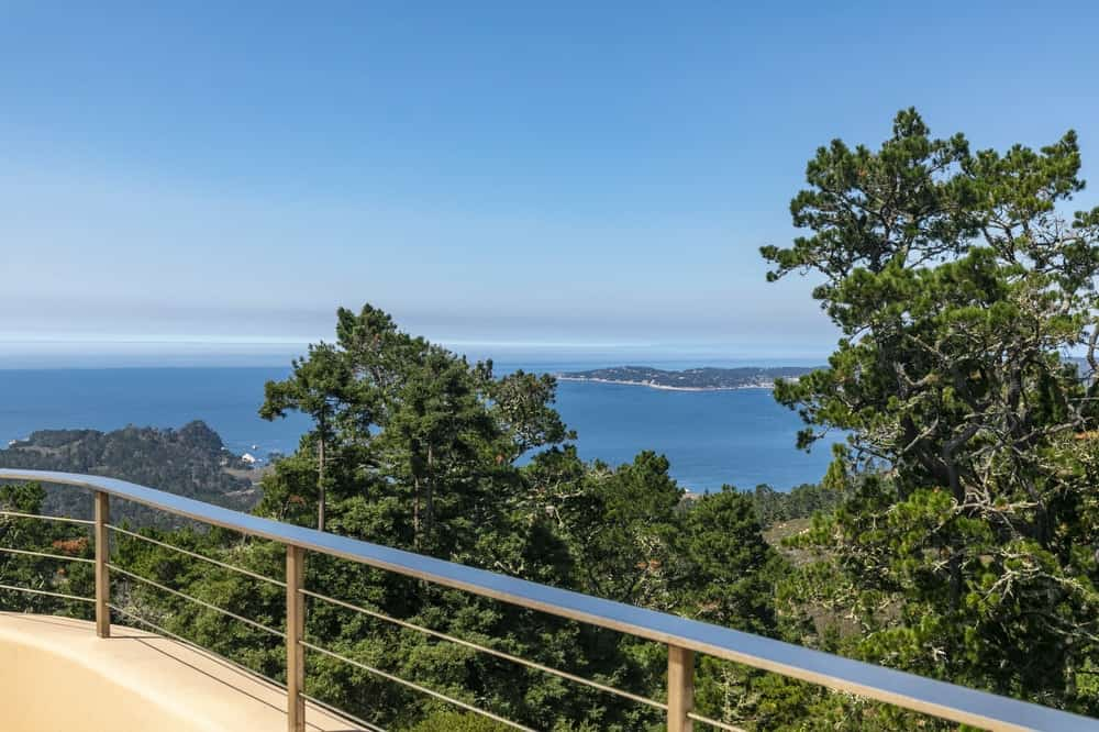 This is the view beyond the steel rails of the outdoor dining area. You can see here the tall treetops and the view of the Pacific Ocean in the distance. Image courtesy of Toptenrealestatedeals.com.