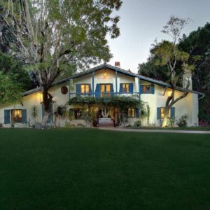 This is a look at the front of the house with a large grass lawn on its front yard. You can also see here the bright colors of the exteriors of the house that stands out with its warm exterior lights. Image courtesy of Toptenrealestatedeals.com.