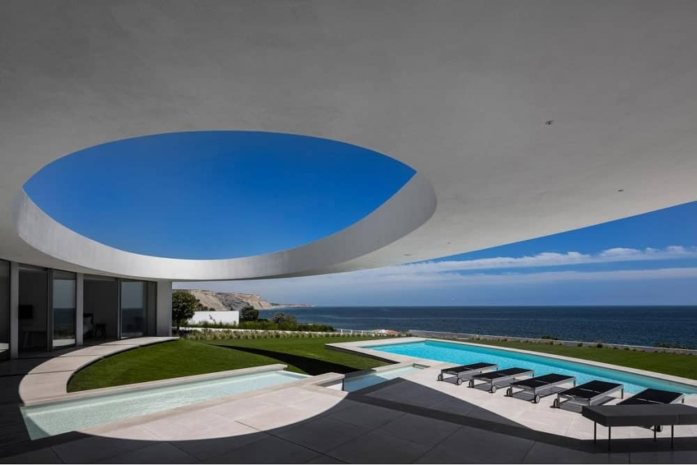 This is a view of the back of the house that has large glass walls facing a covered poolside area that has a unique elliptical design to its concrete cover with a bright tone.