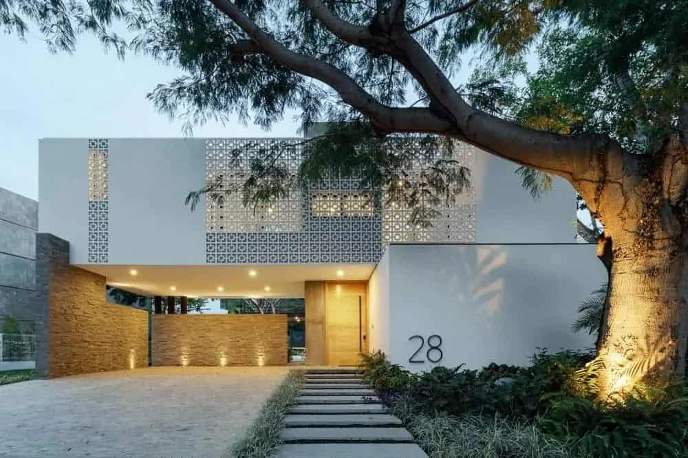 This is a look at the front of the house with white exterior walls complemented by the second level see-through panels that glow warmly along with the warm lighting of the huge carport by the entrance.