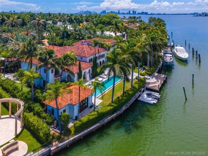 This is an aerial view of the back of the house that has a large swimming pool. The property is lined by tall tropical trees. Image courtesy of Toptenrealestatedeals.com.