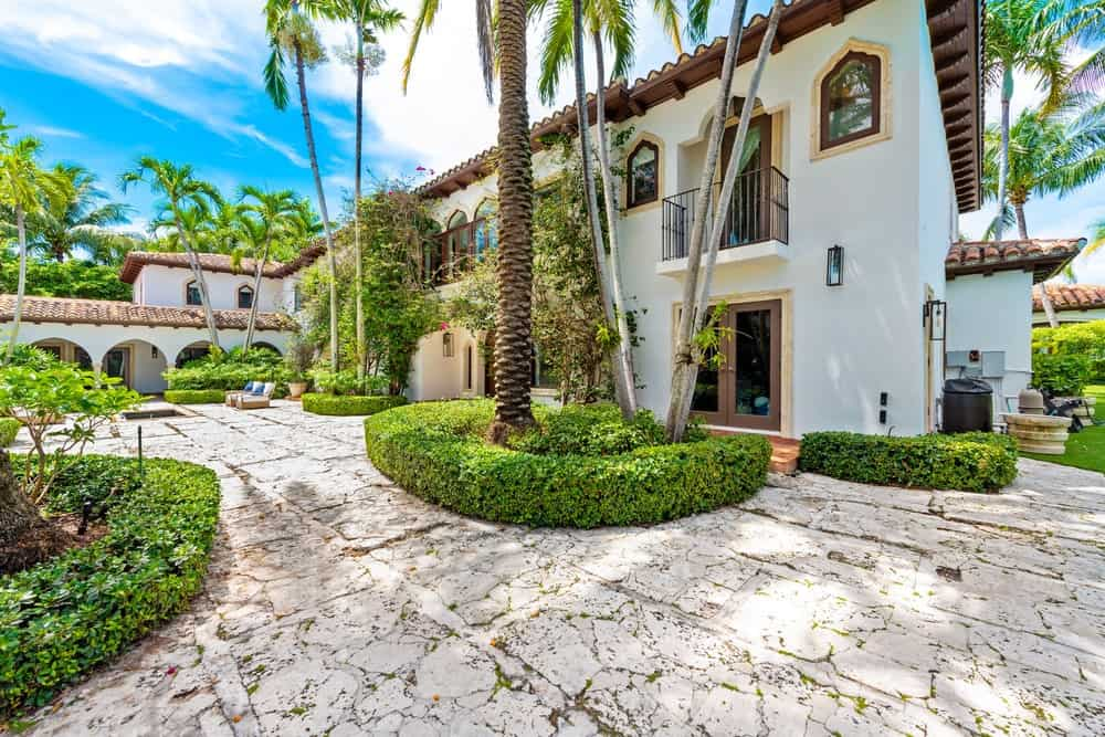 This is a close look at the house exterior with balconies shaded by tall tropical trees surrounded by shrubs. Image courtesy of Toptenrealestatedeals.com.
