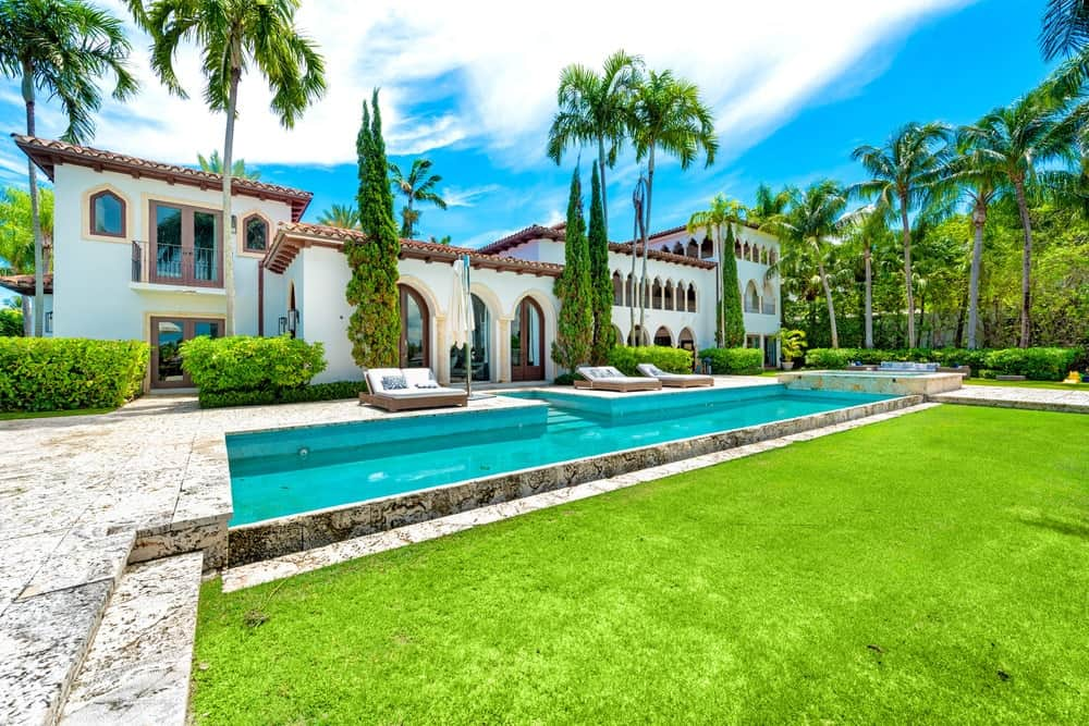 This is a view of the back of the Mediterranean-style home with terracotta roofs that are complemented by the many arches and windows of the exteriors as well as the swimming pool. Image courtesy of Toptenrealestatedeals.com.