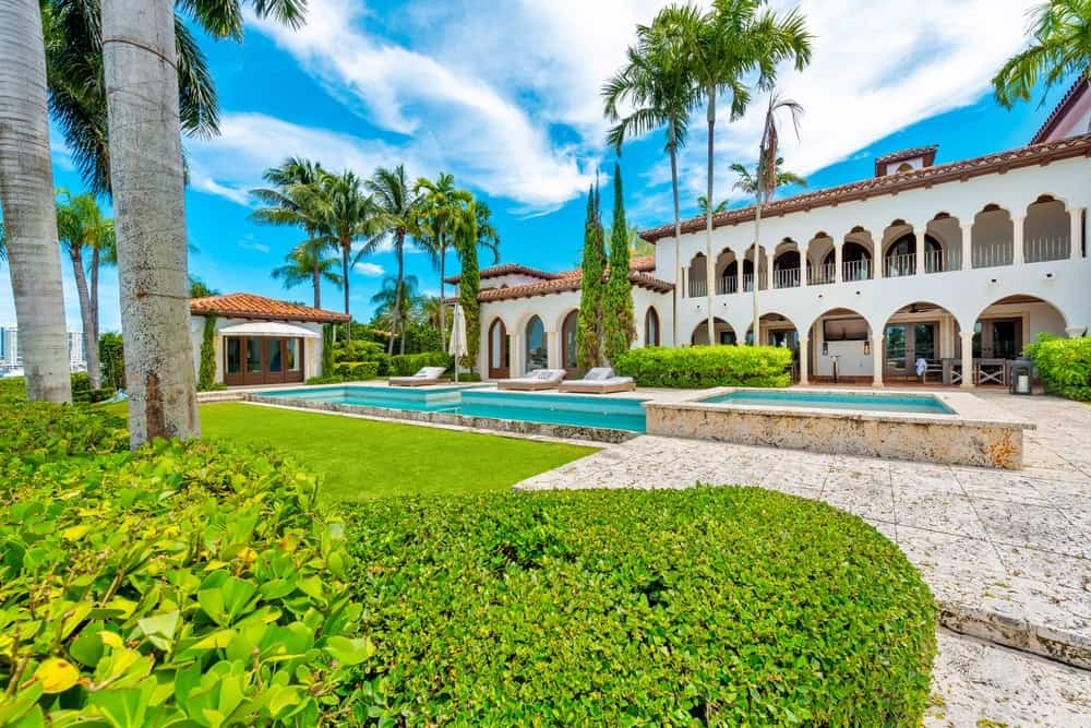 This view of the back of the house features the multiple arches of the house exterior that bring in an abundance of natural lighting for the interiors. Image courtesy of Toptenrealestatedeals.com.