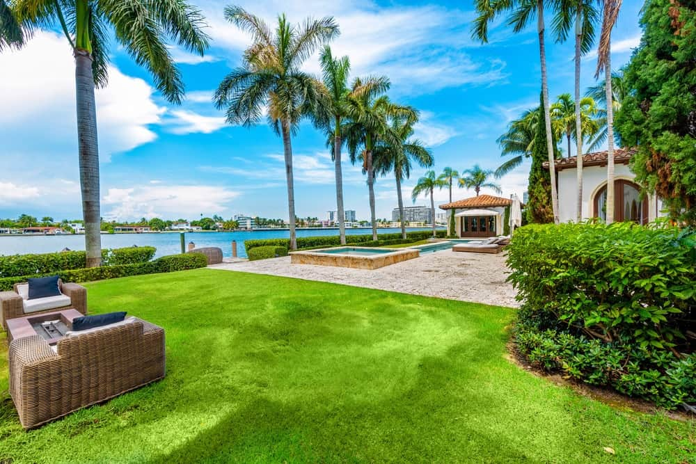 This view of the backyard showcases the lush landscaping that has grass lawns, shrubs and tall tropical trees. Image courtesy of Toptenrealestatedeals.com.