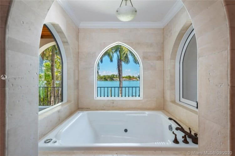 This is the bathroom with a large square bathtub inside a cove with arched windows. Image courtesy of Toptenrealestatedeals.com.
