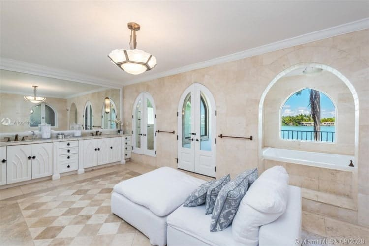 This other view of the primary bathroom showcases a large white daybed across from the vanity area under the semi-flush lighting. Image courtesy of Toptenrealestatedeals.com.