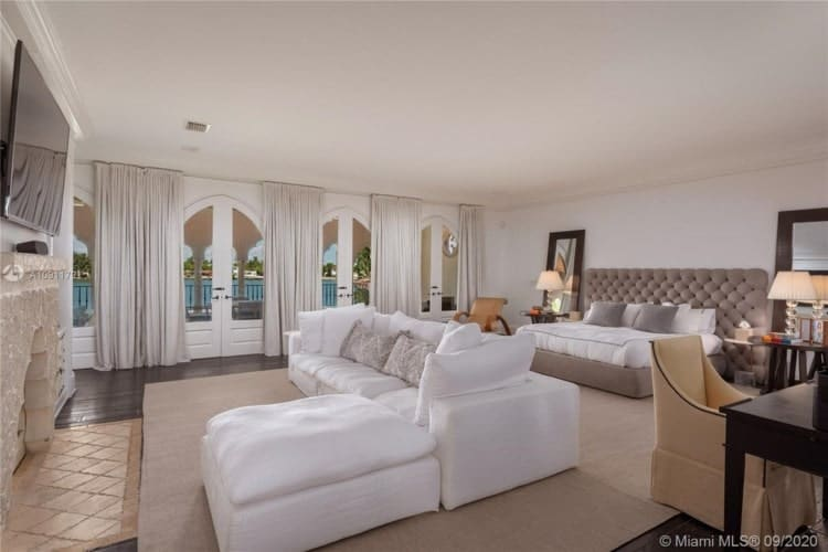 The primary bedroom has a tufted bed and a large white L-shaped sectional sofa across from it at the sitting area. Image courtesy of Toptenrealestatedeals.com.