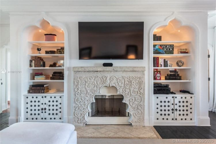 This is the built-in stucture across from the L-shaped sectional sofa of the primary bedroom. It has a fireplace topped with a TV and flanked by shelves. Image courtesy of Toptenrealestatedeals.com.