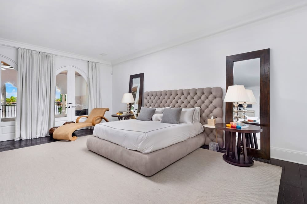 This other bedroom has a gray tufted bed flanked by bedside table, large mirrors and table lamps. Image courtesy of Toptenrealestatedeals.com.