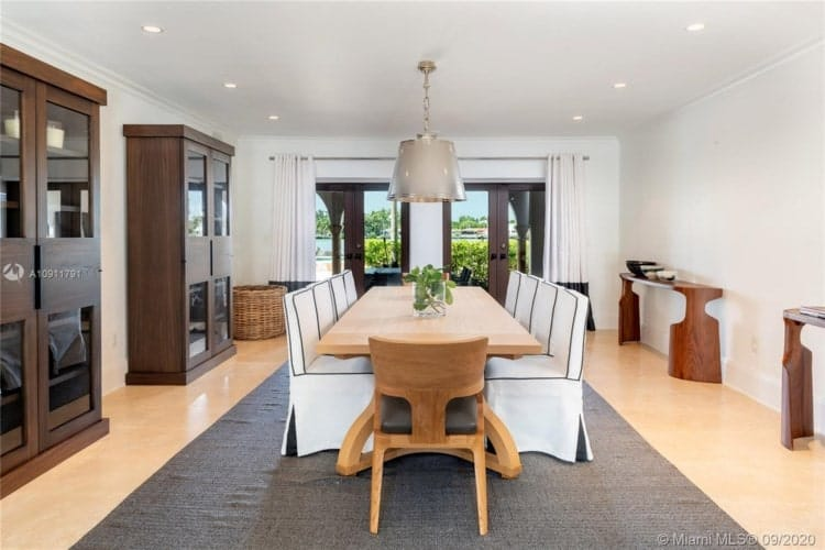 This is the formal dining room with a large wooden dining table surrounded by white chairs that match the white ceiling. Image courtesy of Toptenrealestatedeals.com.