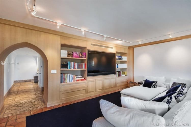 The white tone of the sectional sofa matches well with the walls and ceiling that are complemented by the wooden structure of the TV. Image courtesy of Toptenrealestatedeals.com.