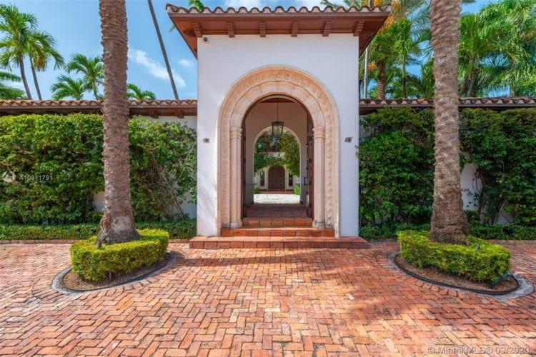 This is a closer look at the main entrance with an archway flanked by tall trees and green landscaping. Image courtesy of Toptenrealestatedeals.com.