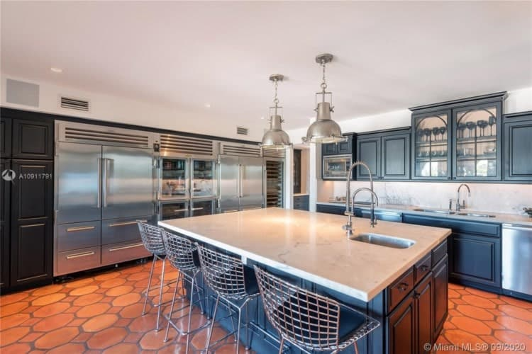 This other view of the kitchen shows that the large kitchen island in the middle has stools for the breakfast bar and topped with pendant lights. Image courtesy of Toptenrealestatedeals.com.
