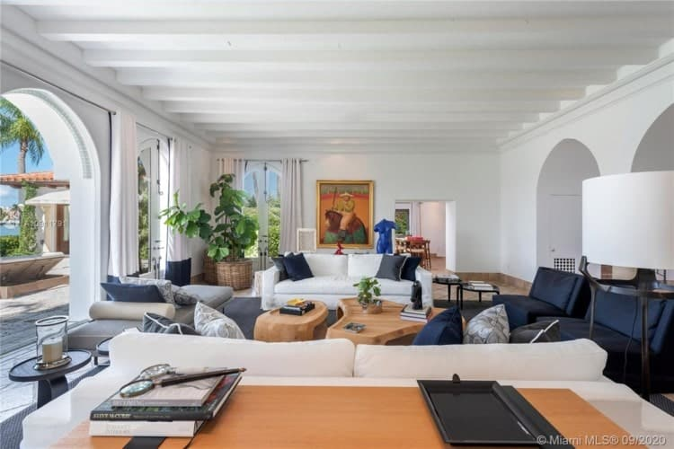 This is the living room that has sofas, coffee table that are complemented by the bright white walls and ceiling and the natural lighting. Image courtesy of Toptenrealestatedeals.com.