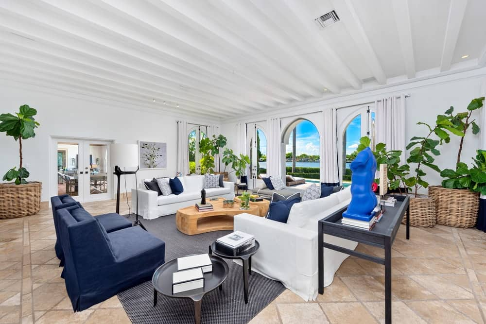 This other view of the living room showcases the bright white beamed ceiling that matches well with the pair of white sofas. Image courtesy of Toptenrealestatedeals.com.